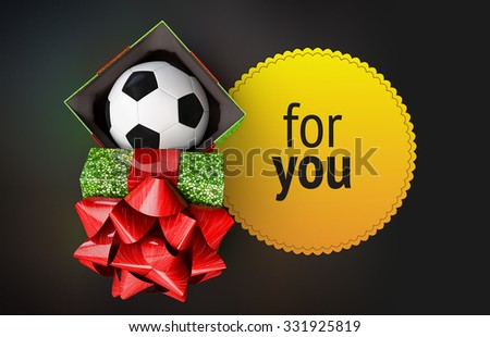 soccer ball at shiny gift box green mosaic texture top view. cover decorated beautiful red bow open and placed next  container. near present is patterned label empty space place congratulatory text - stock photo