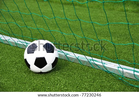 Soccer ball at the goal net - stock photo