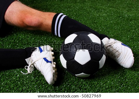 Soccer ball being kicked with soccer boots (football) in a slide tackle on green grass (artificial turf) - stock photo