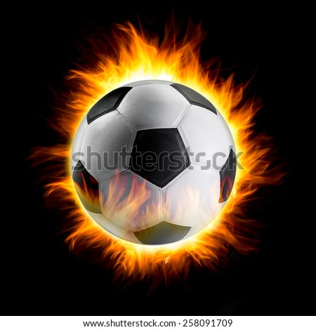 Soccer ball catching fire on black background - stock photo