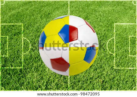 Soccer ball colored by flag of Poland and Ukraine at green grass - stock photo