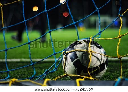 Soccer ball falls into the net - stock photo