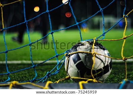 Soccer ball falls into the net, its goal - stock photo