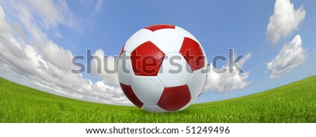 Soccer ball in a green field with blue cloudy sky - stock photo