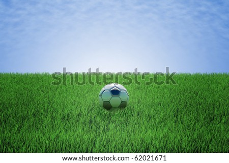 soccer ball in a green field with blue sky - stock photo