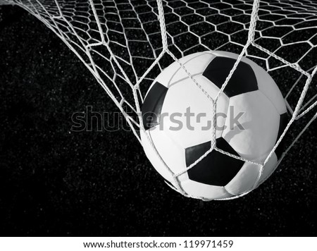 Soccer ball in goal, black and white - stock photo