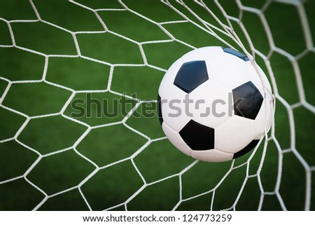 soccer ball in goal net with green grass - stock photo