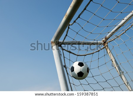 soccer ball in goal on the blue sky background. - stock photo
