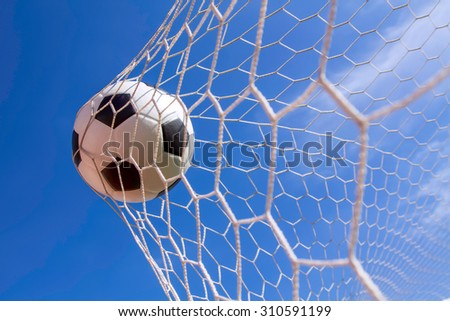 soccer ball in goal on the field - stock photo