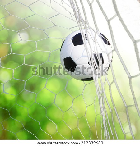 soccer ball in goal with bokeh - stock photo