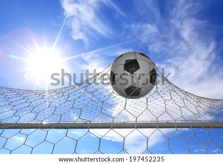 soccer ball in goal with sun  - stock photo