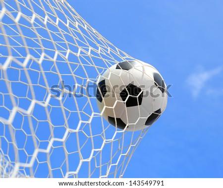 soccer ball in net on blue sky - stock photo