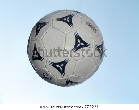Soccer ball in the air with sky in the background - stock photo