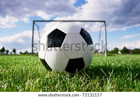 Soccer ball in the grass field - stock photo