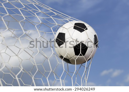 soccer ball in the net on blue sky background - stock photo