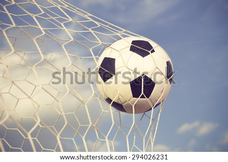 soccer ball in the net on blue sky background vintage color - stock photo