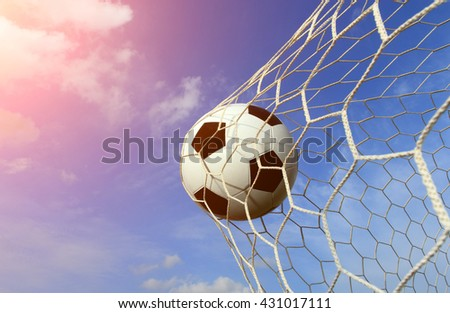 soccer ball into the goal and have an orange light like the sun. - stock photo