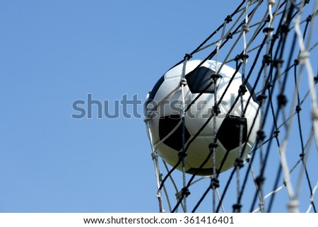 Soccer ball kick in goal with net and sky - stock photo