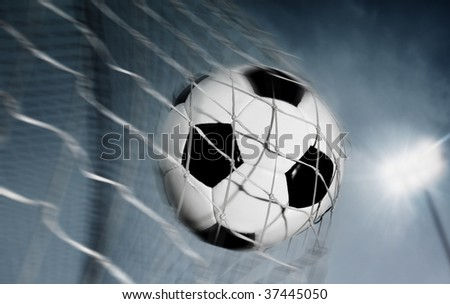 Soccer ball kicked into the back of a goal - stock photo