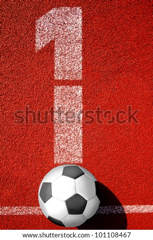soccer ball lies on tartan surface