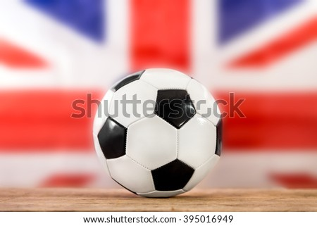 soccer ball on a wooden table, in front of the british flag