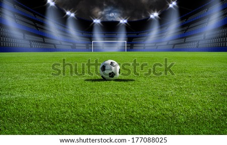 Soccer ball on field in stadium at night - stock photo