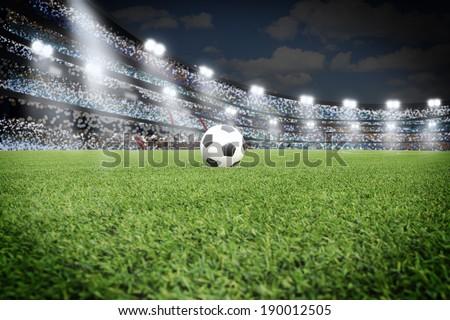 Soccer ball on field in stadium at night - stock photo