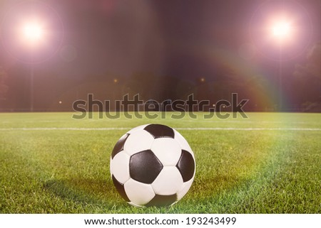soccer ball on field wiht spot lights - stock photo