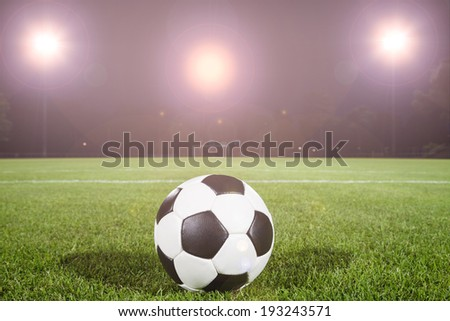 soccer ball on field with light spots - stock photo