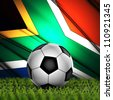 Soccer ball on fresh green grass with South Africa national flag on the background - stock photo