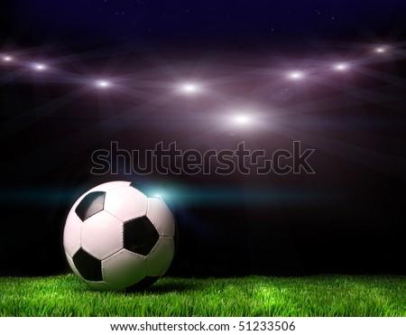 Soccer ball on grass against black background - stock photo