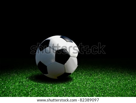 Soccer ball on grass over black background - stock photo