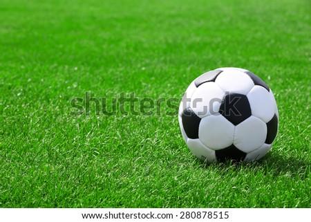 Soccer ball on green field - stock photo
