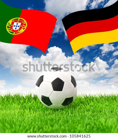 soccer ball on green grass and national flags of germany and portugal over dramatic blue sky