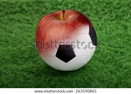 soccer ball on green grass to red apple - stock photo