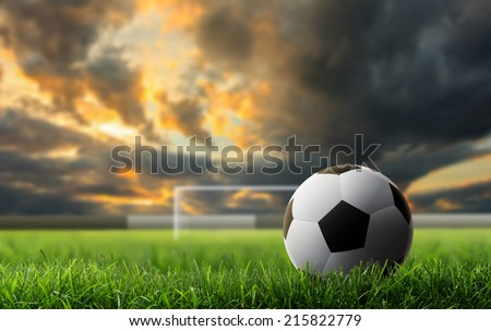 soccer ball on green grass  with sunset background. - stock photo