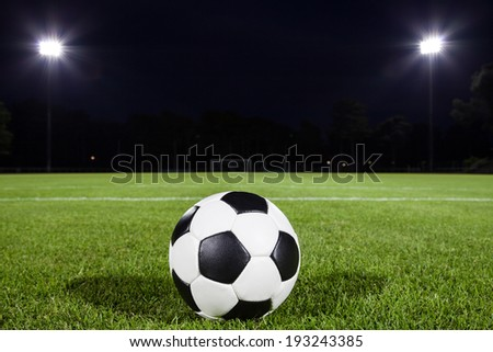 soccer ball on playing field with light spot - stock photo