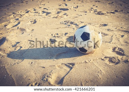Soccer ball on sand (Vintage filter effect used) - stock photo