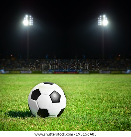 Soccer ball on the field with sport light at stadium night - stock photo