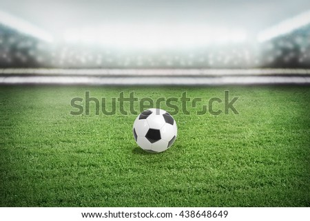 Soccer ball on the football field full of spectators. Stadium in lights of cameras and spotlights. - stock photo