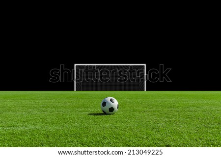 Soccer ball on the green field with black background - stock photo