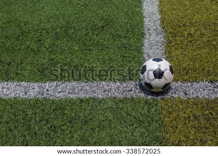 soccer ball on the white line on green soccer field grass background - stock photo