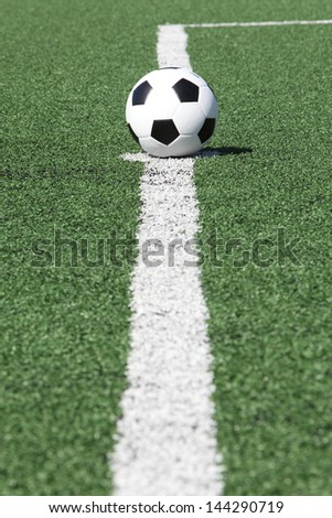 soccer ball on white line in green grass - stock photo