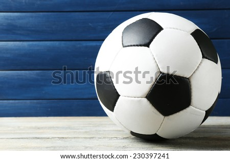 Soccer ball on wooden background - stock photo