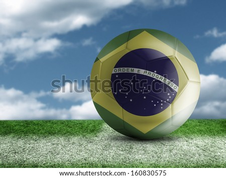 Soccer ball with Brazilian flag in a green field - stock photo