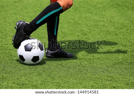 soccer ball with foot of player touching it with adumbration - stock photo