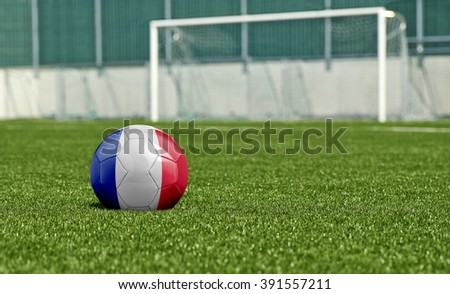 Soccer ball with the flag from France on the green field - stock photo