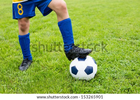 Soccer ball with their feet boy on the football field. - stock photo