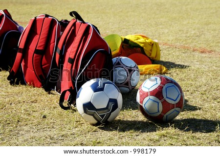 Soccer balls and bags on the sidelines at a youth soccer game. - stock photo