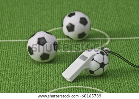 Soccer balls on green soccer meadow with thunderer whistle